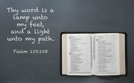 An Opened Bible on a Dark Chalkboard Surface