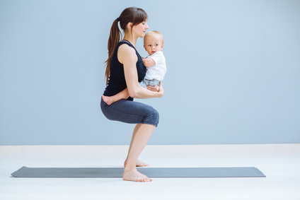 Sport, motherhood and active lifestyle concept - side view of young mother doing yoga with toddler baby at home. Squatting exercise.